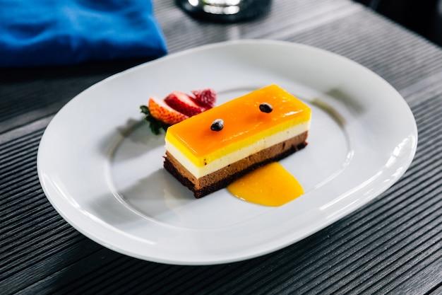 Couche de gâteau comprenant la sauce à l'orange et la garniture au chocolat avec graines de café.