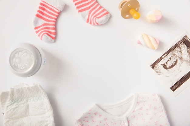 Couche; vêtements pour bébé; guimauve; chaussettes; sucette; image de sonographie et bouteille de lait sur fond blanc
