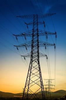 Le coucher du soleil derrière la silhouette des pylônes d'électricité