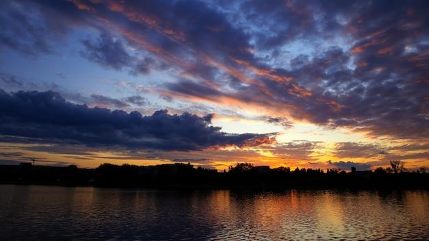Coucher du soleil en moldavie, nuages luxuriants avec une lumière jaune reflétée dans la surface de l'eau au premier plan