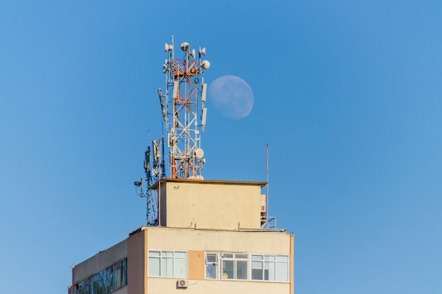 Coucher de lune derrière un bâtiment avec des antennes