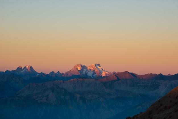 Coucher de soleil sur les alpes ciel coloré, sommets de haute altitude avec glaciers, parc national du massif des écrins, france.