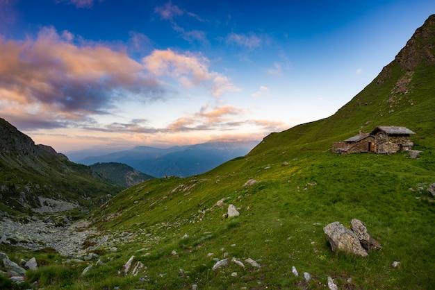 Coucher de soleil sur les alpes, pâturages et prairies avec refuge en refuge
