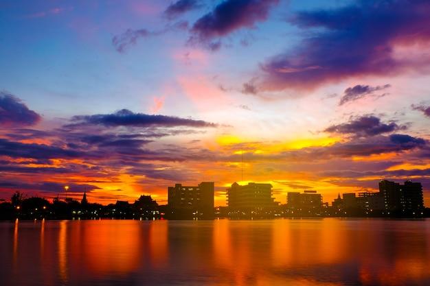 Le coucher de soleil au bord du lac dans le parc de la ville est l'arrière-plan.