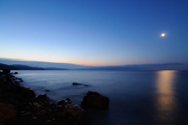 Coucher de soleil au bord de la mer, plage parsemée de pierres