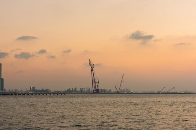 Coucher de soleil au port de dubaï, émirats arabes unis. silhouette de grues sur un fond de ciel lumineux