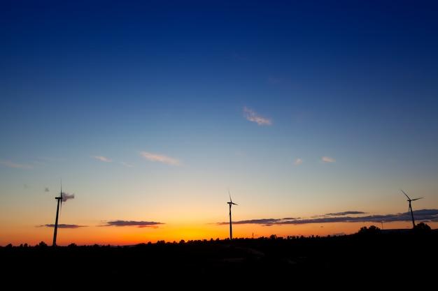 Coucher de soleil bleu orange avec des moulins à vent électriques