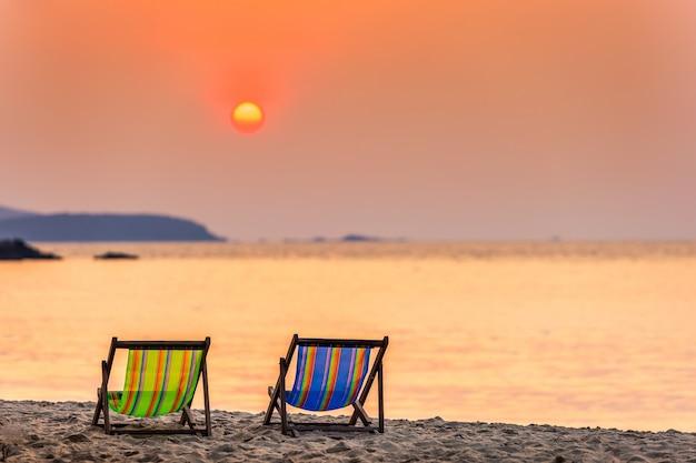 Coucher de soleil sur des chaises longues sur la plage