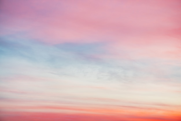Coucher de soleil ciel avec des nuages légers orange rose. dégradé coloré ciel bleu lisse. fond naturel du lever du soleil. paradis incroyable au matin. ambiance de soirée légèrement nuageuse. temps magnifique à l'aube.