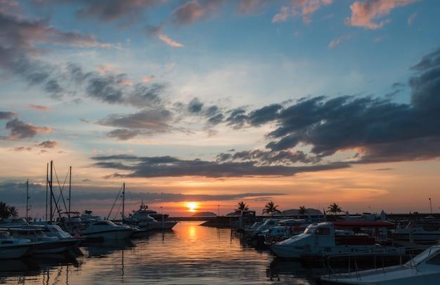 Coucher de soleil avec ciel nuageux sur la jetée avec des yachts