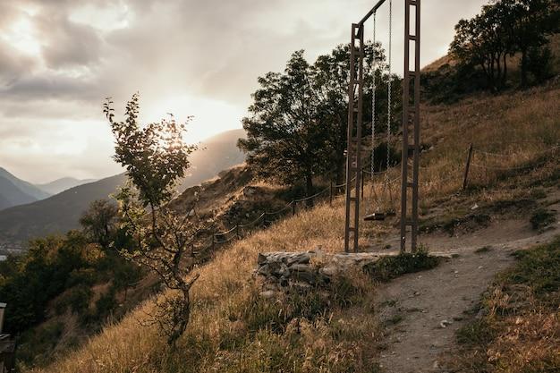 Coucher de soleil sur une colline avec une balançoire suspendue. téberda