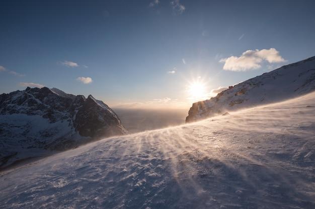 Coucher de soleil sur la colline enneigée dans le blizzard au coucher du soleil