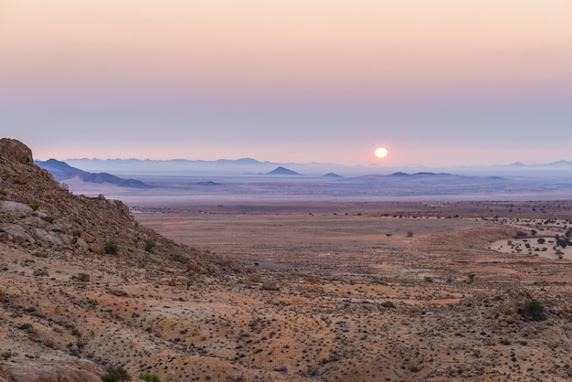 Coucher de soleil coloré sur le désert du namib, aus, namibie, afrique. ciel rouge orange violet clair à l'horizon, rochers rougeoyants et canyon au premier plan.