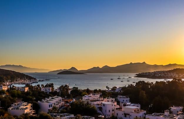 Coucher de soleil coloré et lumineux dans la magnifique baie de la mer égée avec des îles, des montagnes et des bateaux