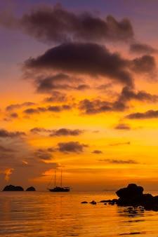 Coucher de soleil coloré sur une plage tropicale. coucher de soleil orange sur l'océan. coucher de soleil coloré sous les tropiques. dans l'eau est un voilier. voilier silhouette avec mâts