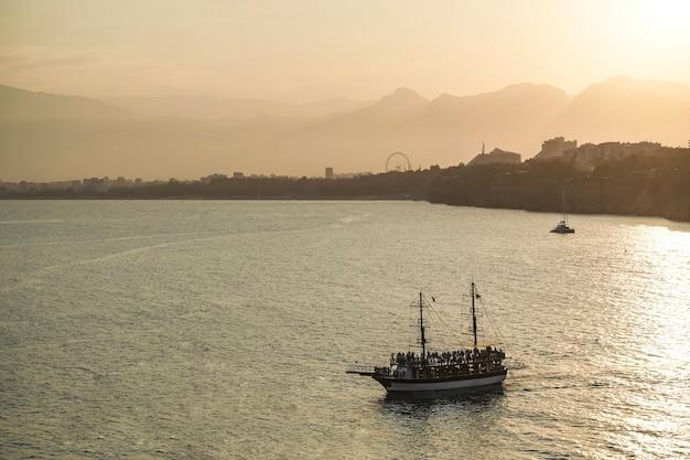 Coucher de soleil sur la côte méditerranéenne en turquie navire en mer avec des touristes sur fond de su...