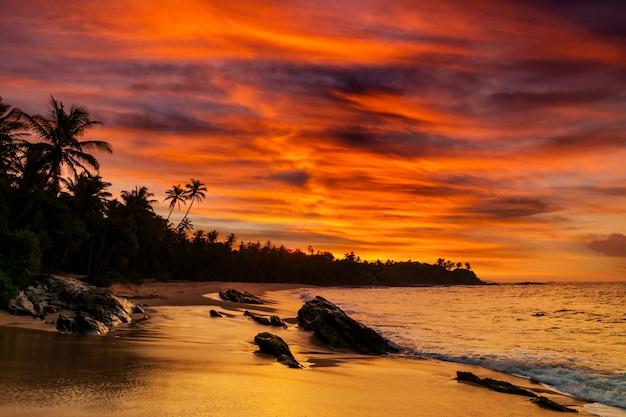 Coucher de soleil sur la côte rocheuse de la mer tropicale