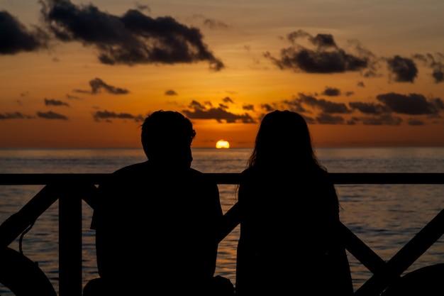 Coucher de soleil et couple sur la plage à la recherche au loin