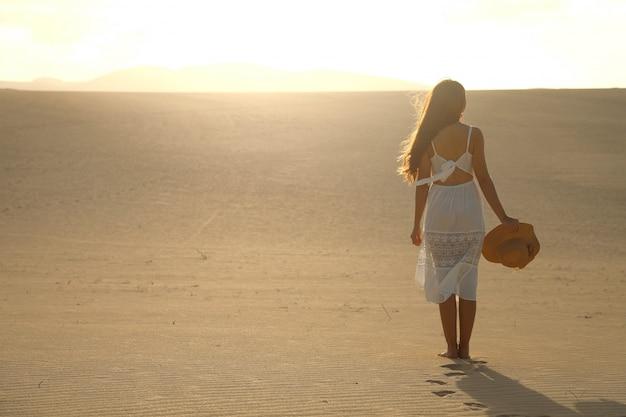 Coucher de soleil dans le désert. jeune femme en robe blanche marchant dans les dunes du désert avec des pas dans le sable pendant le coucher du soleil. fille qui marche sur le sable doré sur corralejo dunas, fuerteventura.