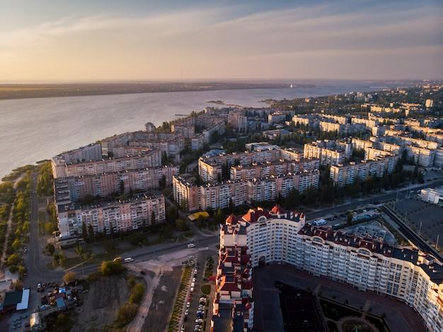 Coucher de soleil dans le sud de l'ukraine, vue aérienne sur des bâtiments résidentiels avec rivière