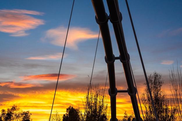 Coucher de soleil dans une ville méditerranéenne avec la silhouette de la structure métallique d'un pont suspendu