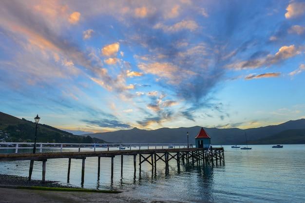 Coucher de soleil derrière les montagnes dans le port d'akaroa, nouvelle-zélande