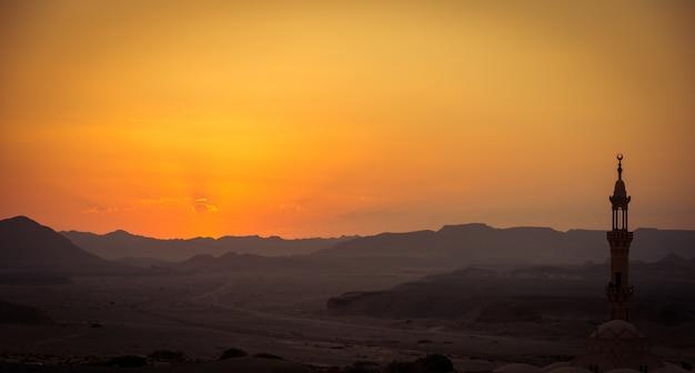 Coucher soleil sur le désert avec mosquée musulman au premier plan