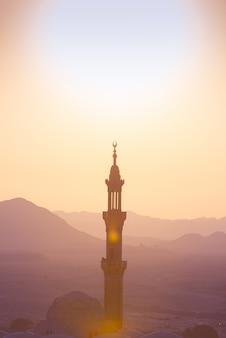 Coucher soleil sur le désert avec mosquée musulmane