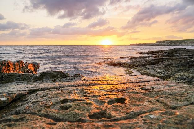 Coucher de soleil doré sur la mer sur la roche de pierre de tarkhankut, crimée
