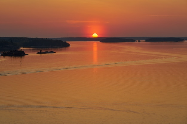 Coucher de soleil doré à naantali, finlande. réflexion du soleil sur l'eau. copiez l'espace.