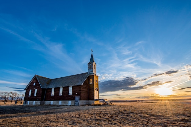Coucher de soleil sur l'église catholique st. joseph parish à frenchville, saskatchewan