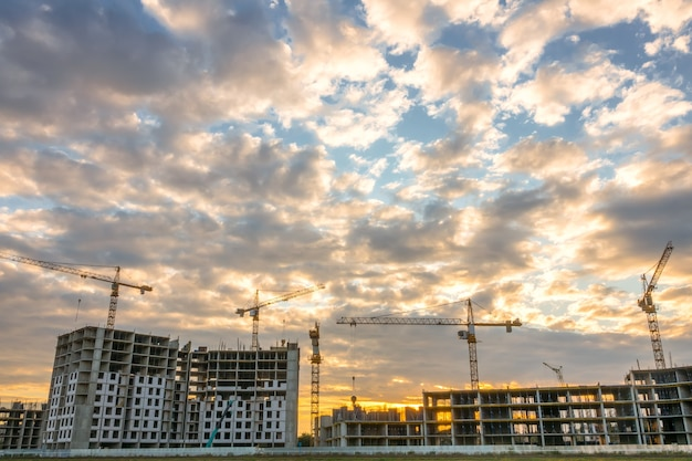 Coucher de soleil d'été à la construction de bâtiments résidentiels. de nombreuses grues fonctionnent