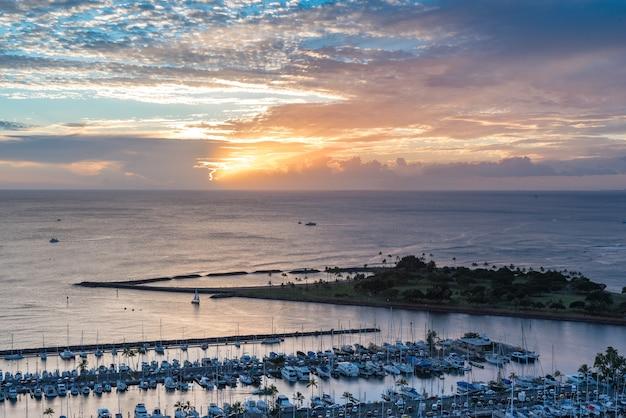 Un coucher de soleil expansif sur les yachts du petit port de plaisance d'ala wai et de l'île magique