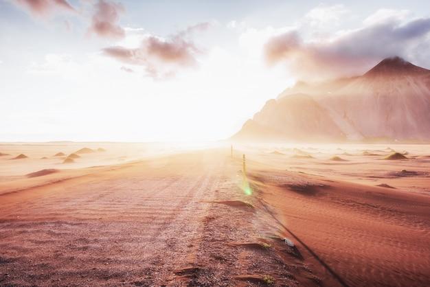 Coucher de soleil fantastique sur les montagnes et dunes de sable volcaniques sur la plage de stokksness. une chaude journée et un désert