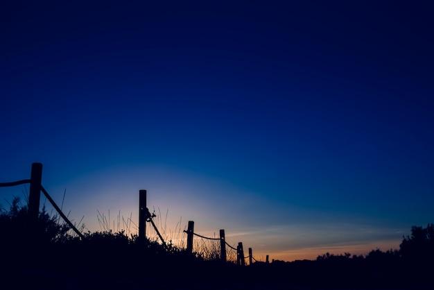 Coucher de soleil froid avec la silhouette des dunes de la plage