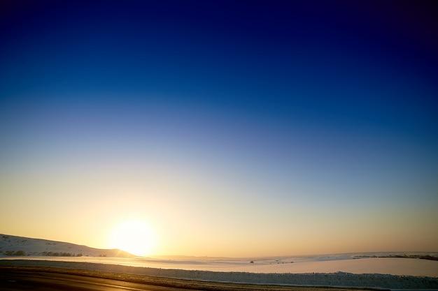 Coucher de soleil d'hiver sur fond de montagnes enneigées