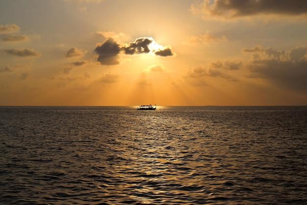 Coucher de soleil sur l'île des maldives avec bateau, vue depuis le complexe de villas sur l'eau.
