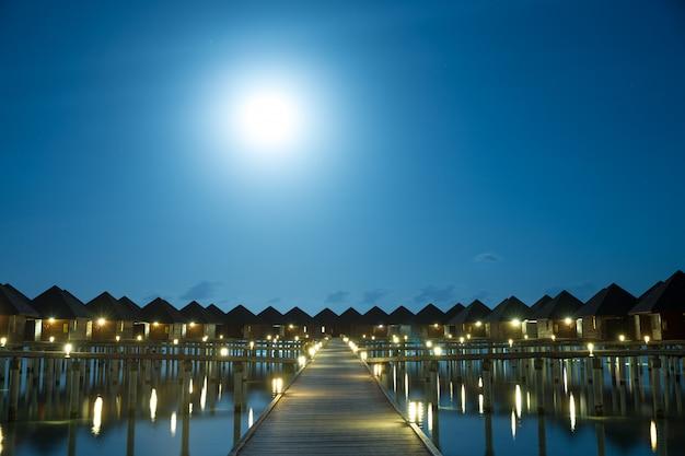 Coucher de soleil sur l'île des maldives, complexe de villas sur l'eau de luxe et jetée en bois. beau ciel et nuages et fond de plage pour les vacances d'été et le concept de voyage