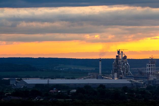 Coucher de soleil jaune sur paysage industriel avec des cheminées d'usine et des tuyaux de fumée polluant l'atmosphère.