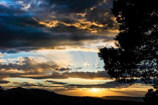 Coucher de soleil un jour avec des nuages et des rayons de soleil qui en sortent dans la montagne.