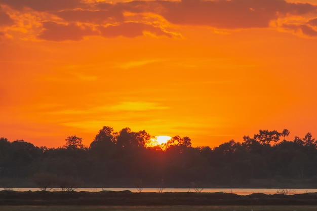 Coucher de soleil sur le lac beau coucher de soleil derrière les nuages au-dessus du fond de paysage de lac. ciel dramatique avec nuage au coucher du soleil