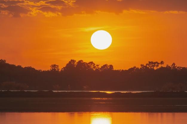 Coucher de soleil sur le lac. beau coucher de soleil derrière les nuages au-dessus du paysage sur le lac
