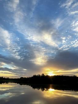 Coucher de soleil sur le lac. le soleil se couche derrière la forêt silhouettée à l'horizon. le ciel couvert dramatique se reflète sur la surface de l'eau du lac