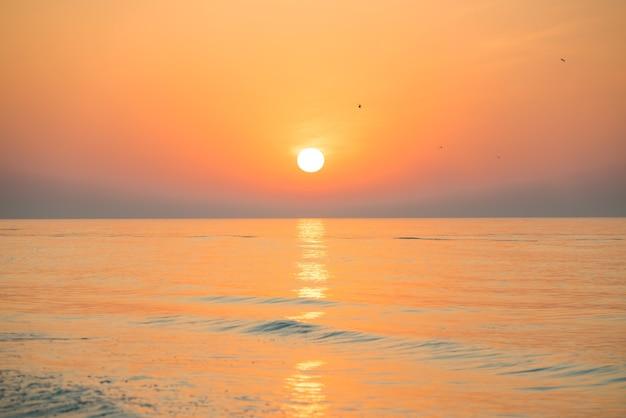 Coucher de soleil ou lever de soleil sur la mer avec soleil sur un beau ciel dramatique