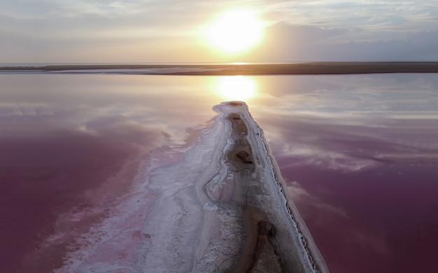 Coucher de soleil lumineux sur un lac rose, flare orange sur l'eau rose de la plage.