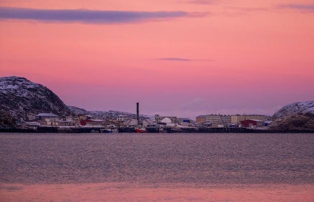 Coucher de soleil magique et coloré dans le nord polaire. vue de la ville d'hiver de teriberka. russie.