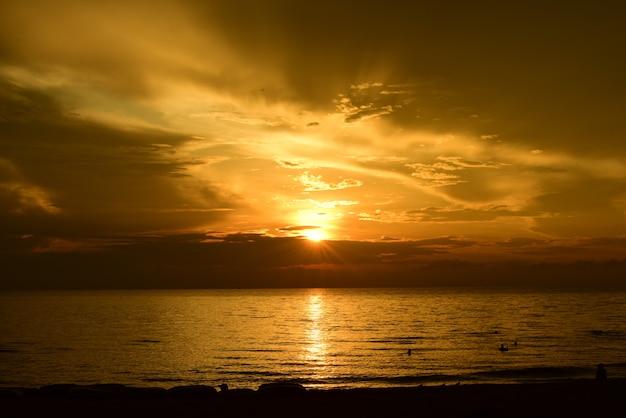Coucher de soleil sur la magnifique vue sur la plage parmi les nombreuses personnes qui viennent jouer dans la mer avant le coucher du soleil. silhouette du coucher de soleil sur la plage.