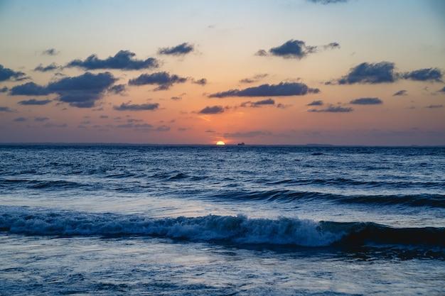 Coucher de soleil, mer bleue, bateau de fond, ciel orange avec nuages, ville de são luis, état de maranhão