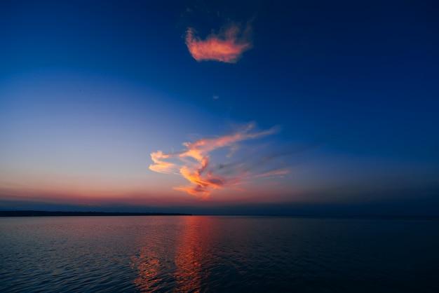 Coucher de soleil sur la mer avec ciel bleu et nuages se reflétant dans l'eau