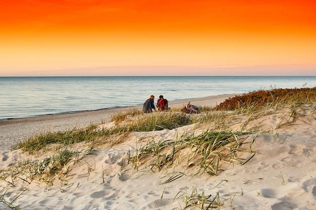 Coucher de soleil sur la mer. jeune couple sur une plage au coucher du soleil. romantique.